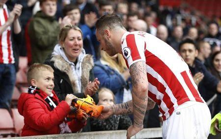Stoke City's Marko Arnautovic gives his boots to a young fan after the game