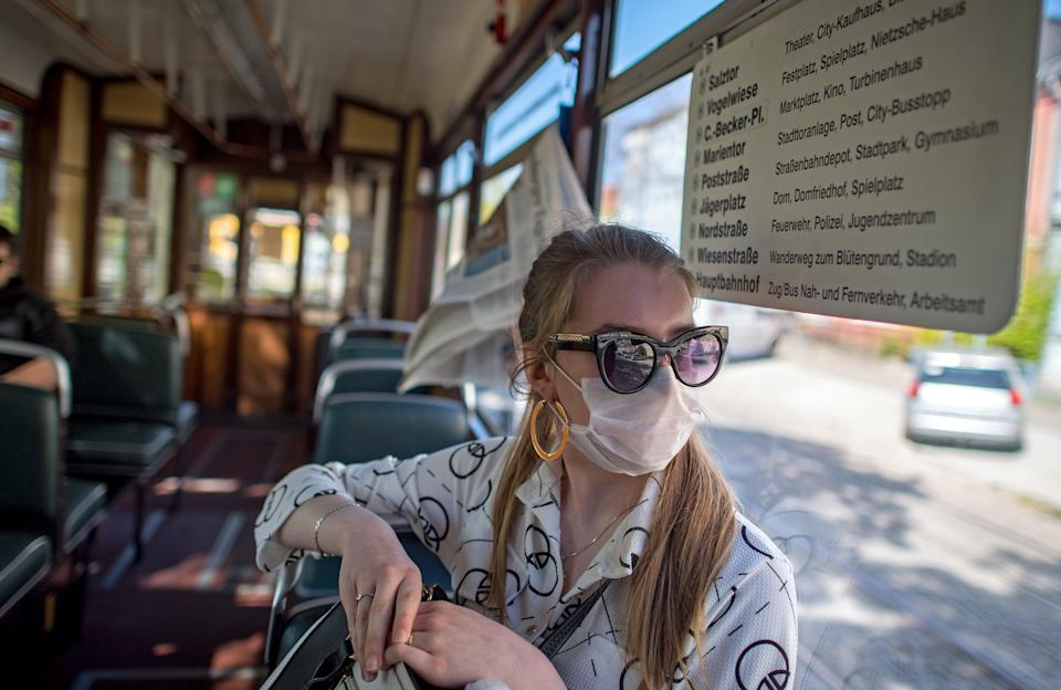 """21 April 2020, Saxony-Anhalt, Naumburg: Josephine Nauke sits in the historic tram in Naumburg with a face mask. The railcar type """"Gotha"""" was built in 1959 and runs regularly on line four between Salztor and the main station. Even in the smallest tram operation in Germany, passengers will be required to wear masks from Thursday (23.04.2020). The federal state of Saxony-Anhalt had decided to make it compulsory to wear a face mask on buses and trains and when shopping on Tuesday. Photo: Hendrik Schmidt/dpa-Zentralbild/dpa (Photo by Hendrik Schmidt/picture alliance via Getty Images)"""