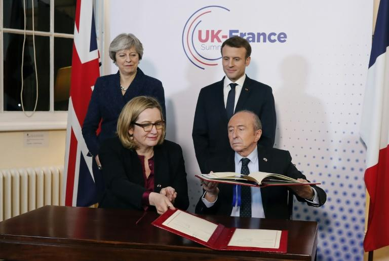 The British and French interior ministers, Amber Rudd amd Gerard Collomb, sign the new border security accord as Theresa May and Emmanuel Macron look on approvingly