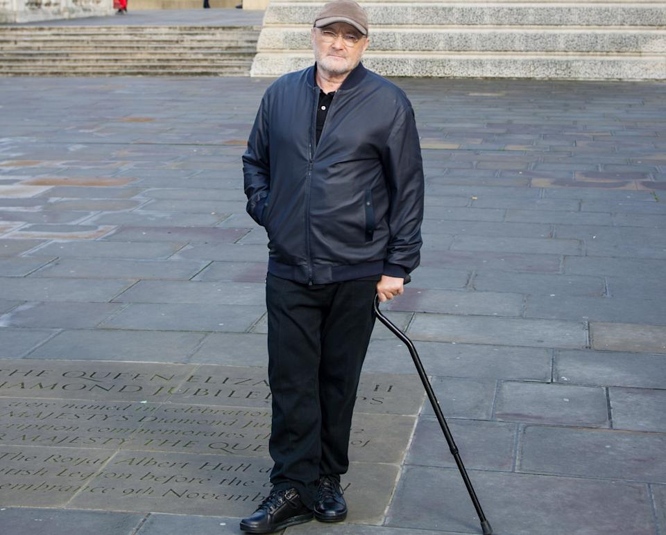 Phil Collins has walked with a stick for several years due to back pain (Credit: PA)