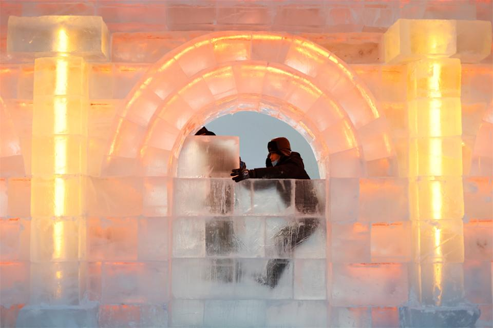 Workers place an ice block onto an ice structure