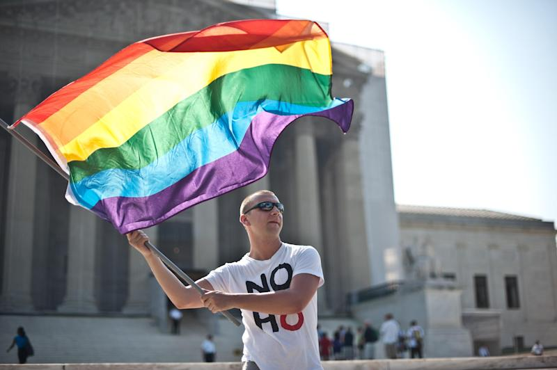 A gay rights activist waves a rainbow flag in front of the US Supreme Court in Washington, DC on June 25, 2013