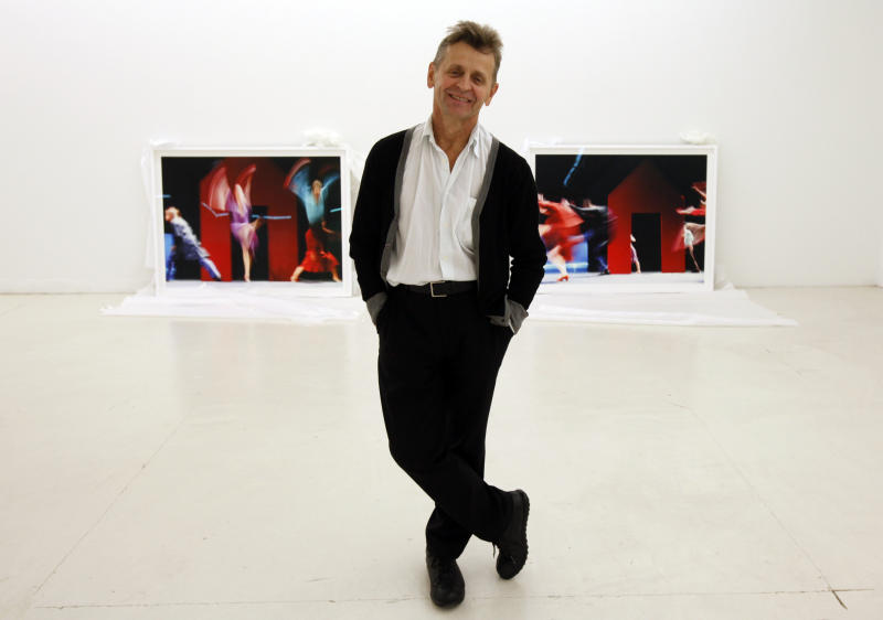 """In this Tuesday, Feb. 21, 2012 photo, dancer Mikhail Baryshnikov, poses with two of the photographs he will be exhibiting at the Gary Nader Art Centre in Miami. The show, which opens Friday, Feb. 24, is titled """"Dance This Way"""" and features large-scale photographs of ethnic, hip-hop, ballet, modern and popular dances performed on stage by professionals and in nightclubs by amateurs. (AP Photo/Wilfredo Lee)"""