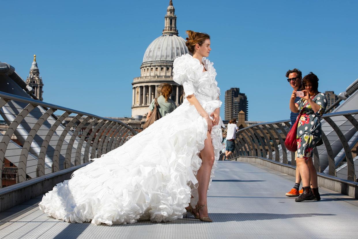 EDITORIAL USE ONLY Jemima Hambro models, on the Millennium Bridge in London, a wedding dress designed by Tom Silverwood and made from over 1,500 unwanted face masks, for wedding planning website, Hitched, to celebrate all restrictions on weddings lifting in England from Monday. Issue date: Monday July 19, 2021.
