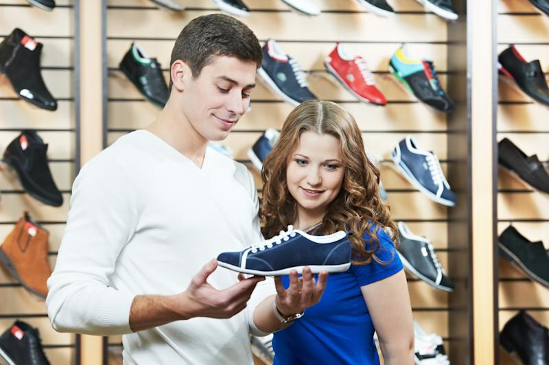 man and woman looking at tennis shoe in a retail store.