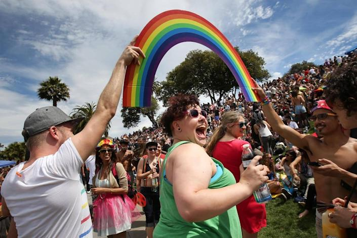 Daniela Lopez smiles as she walks under a rainbow held by two men during a gay pride celebration in Dolores Park on June 27, 2015 (Elijah Nouvelage/Getty Images)