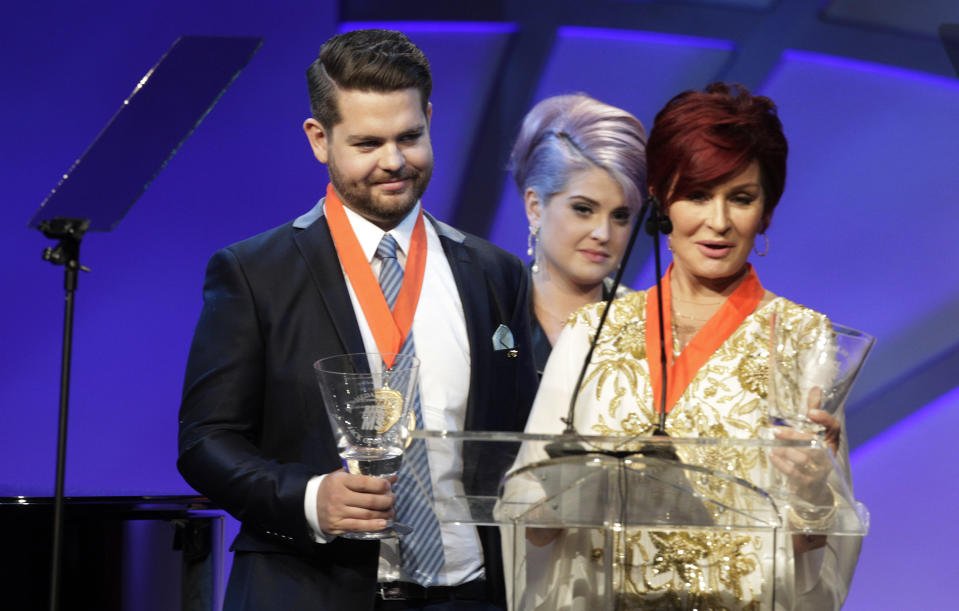 Kelly Osbourne (C) looks on as her mother Sharon Osbourne (R) and brother Jack Osbourne accept the Race to Erase MS Medal of Hope Award at the 20th annual Race to Erase MS benefit gala in Los Angeles, California May 3, 2013. The event raises money to fund research to find a cure for Multiple Sclerosis. Jack Osbourne is being treated for MS. REUTERS/Fred Prouser (UNITED STATES - Tags: ENTERTAINMENT HEALTH)