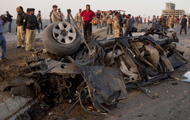 Pakistani investigators look at a vehicle destroyed by a bombing in Karachi, Pakistan, Thursday, Jan. 9, 2014. Police said a car bomb has killed a senior police investigator known for arresting dozens of Pakistani Taliban, as well as two other officers. (AP Photo/Shakil Adil)