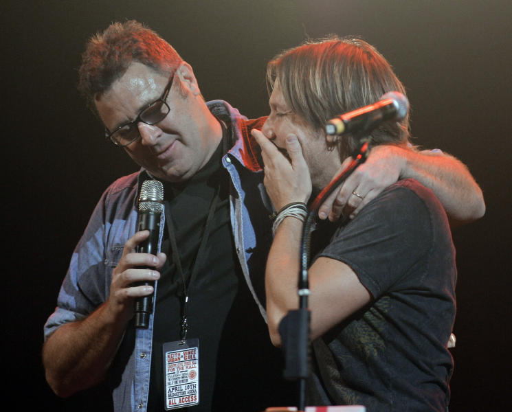 Keith Urban, right, is congratulated by Vince Gill, left, after it was announced that Urban has been selected to become a member of the Grand Old Opry during the All for the Hall concert on Tuesday, April 10, 2012, in Nashville, Tenn. The concert is a benefit for the Country Music Hall of Fame and Museum. (AP Photo/Mark Humphrey)