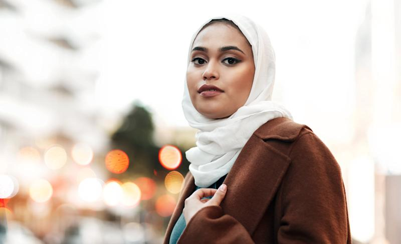 Cropped shot of an attractive young woman wearing a hijab and standing alone while touring the city