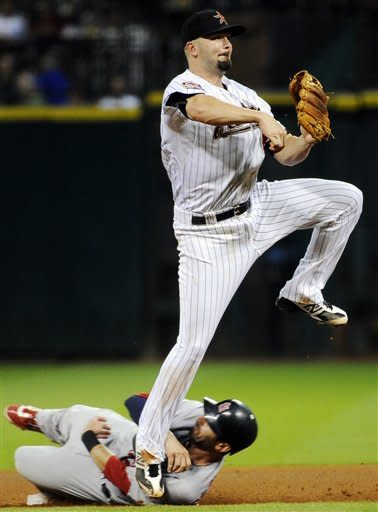 Houston Astros second baseman Scott Moore, right, hops over St. Louis Cardinals' Daniel Descalso as he throws to first base to complete the double play on Pete Kozma in the fourth inning of a baseball game, Monday, Sept. 24, 2012, in Houston. (AP Photo/Pat Sullivan)