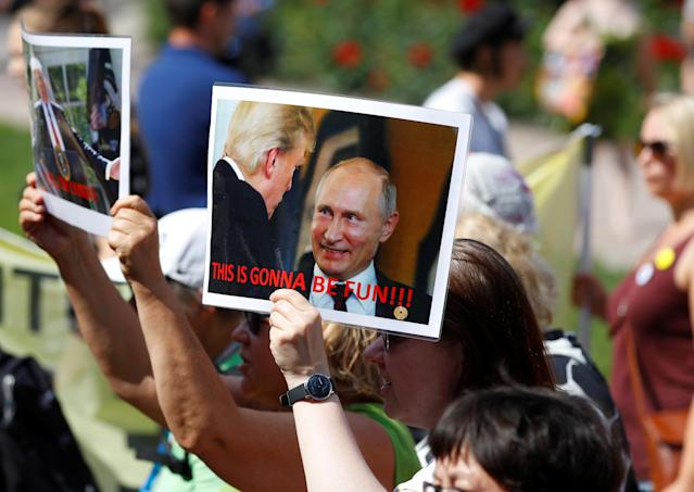 "<p>People carry pictures of Donald Trump and Vladimir Putin as they attend 'Helsinki Calling' protest ahead of meeting between the President Donald Trump and Russian President Vladimir Putin in Helsinki, Finland July 15, 2018. The banner reads ""Worse than each other"". (Photo: Leonhard Foeger/Reuters) </p>"
