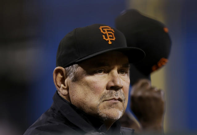 San Francisco Giants manager Bruce Bochy watches from the dugout during the third inning of a spring exhibition baseball game against the Oakland Athletics in San Francisco, Friday, March 28, 2014. (AP Photo/Jeff Chiu)