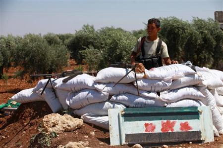 A Free Syrian Army member is seen behind sandbags at a checkpoint during a siege on the Kurdish city of Afrin, which is under the control of the Kurdistan Workers' Party (PKK), in the Aleppo countryside