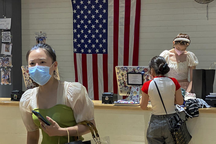 """A woman wearing a face mask visits a fashion boutique in Beijing, Sunday, July 11, 2021. China on Sunday said it will take """"necessary measures"""" to respond to the U.S. blacklisting of Chinese companies over their alleged role in abuses of Uyghur people and other Muslim ethnic minorities. (AP Photo/Andy Wong)"""