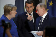 German Chancellor Angela Merkel listens to French President Emmanuel Macron, center, and Russian President Vladimir Putin during a joint press conference with Ukrainian President Volodymyr Zelenskiy, at the Elysee Palace in Paris, Monday Dec. 9, 2019. Russian President Vladimir Putin and Ukrainian President Volodymyr Zelenskiy met for the first time Monday at a summit in Paris to try to end five years of war between Ukrainian troops and Russian-backed separatists. (Charles Platiau/Pool via AP)