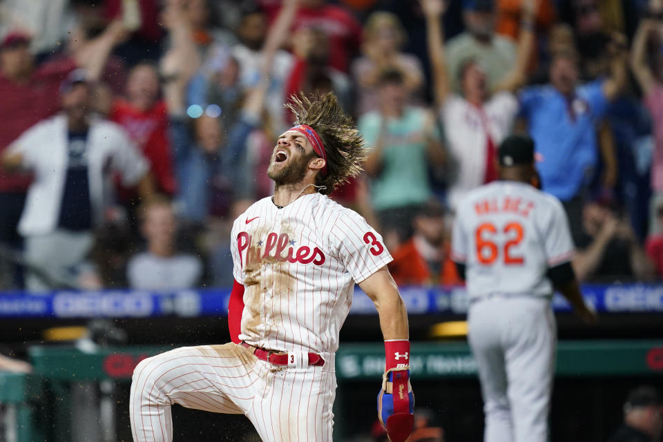 Philadelphia Phillies' Bryce Harper celebrates after scoring the game-winning run on a two-run triple by J.T. Realmuto during the 10th inning of an interleague baseball game against the Baltimore Orioles, Tuesday, Sept. 21, 2021, in Philadelphia. (AP Photo/Matt Slocum)