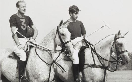 Prince Philip and a young Charles on horseback playing polo in 1966