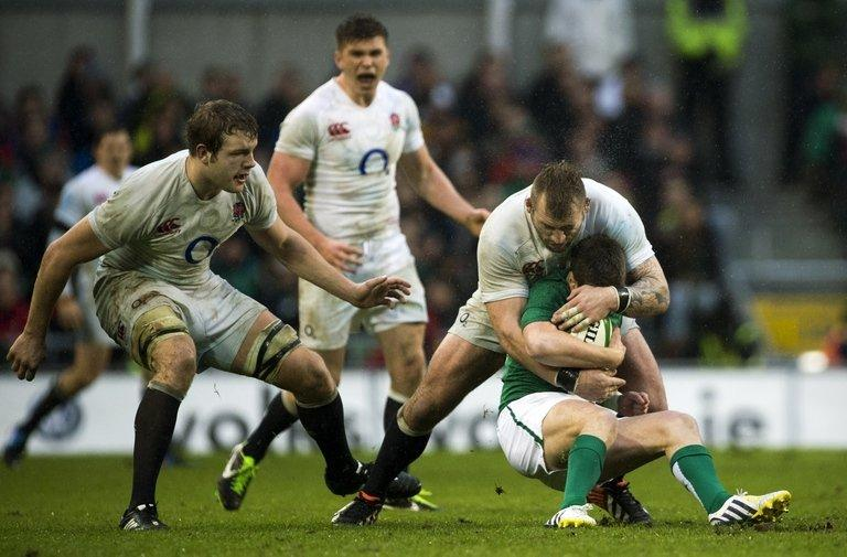 England's Joe Marler (2nd R) tackles Ireland's Ronan O'Gara, in Dublin, on February 10, 2013
