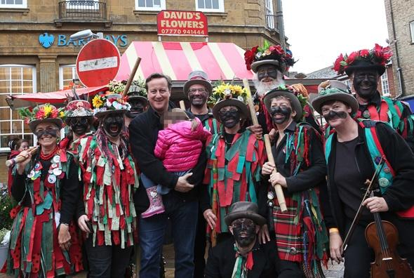 David Cameron poses with blacked-up Morris dancers at festival
