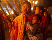 An Indian tribal woman carries a child as she participates in a torch light procession to protest against the Citizenship Amendment Bill (CAB) in Gauhati, India, Monday, Dec. 9, 2019. The bill that seeks to grant Indian citizenship to non-Muslim refugees from Pakistan, Bangladesh and Afghanistan is being debated in the Indian Parliament. (AP Photo/Anupam Nath)