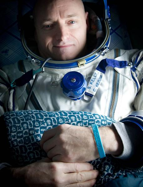 "Expedition 26 Commander Scott Kelly wears a blue wrist band that has a peace symbol, a heart and the word ""Gabby"" to show his love of his sister-in-law U.S. Rep. Gabrielle Giffords as he rests shortly after he and cosmonauts Oleg Skripochka and"