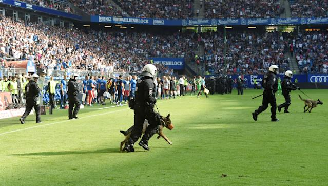 Soccer Football - Bundesliga - Hamburger SV v Borussia Moenchengladbach - Volksparkstadion, Hamburg, Germany - May 12, 2018 Riot police and police dogs run on the pitch in reaction to fan trouble REUTERS/Fabian Bimmer DFL RULES TO LIMIT THE ONLINE USAGE DURING MATCH TIME TO 15 PICTURES PER GAME. IMAGE SEQUENCES TO SIMULATE VIDEO IS NOT ALLOWED AT ANY TIME. FOR FURTHER QUERIES PLEASE CONTACT DFL DIRECTLY AT + 49 69 650050