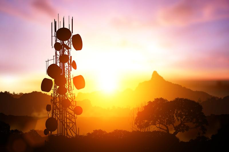 A fully stacked cell tower in silhouette against a colorful sunrise.