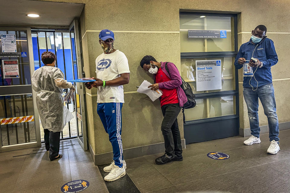 People who were just tested for COVID-19 wait in line to make payment for the test at a private laboratory in Johannesburg, South Africa, Saturday Dec. 19, 2020. South Africa is bracing for its second wave, as many people will travel across provinces for vacations and visiting their families. (AP Photo/Jerome Delay)