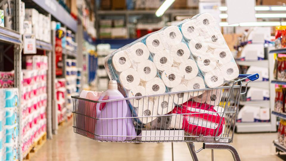 Shopping cart full with products in a large supermarket.