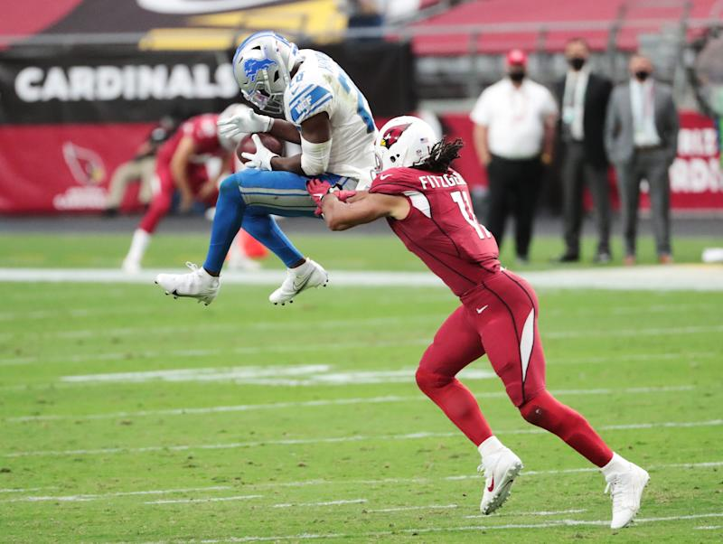 Cardinals wide receiver Larry Fitzgerald breaks up a possible interception by Lions strong safety Duron Harmon during the third quarter of the Lions' 26-23 win on Sunday, Sept. 27, 2020, in Glendale, Ariz.