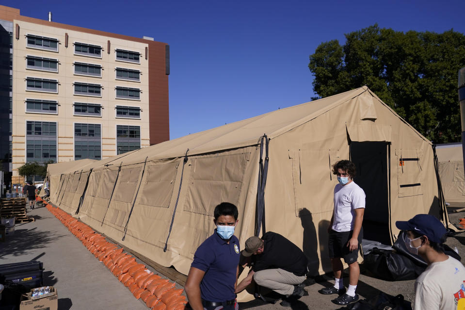 Engineers and volunteers stand outside a mobile field hospital at UCI Medical Center, Monday, Dec. 21, 2020, in Orange, Calif. California's overwhelmed hospitals are setting up makeshift extra beds for coronavirus patients, and a handful of facilities in hard-hit Los Angeles County are drawing up emergency plans in case they have to limit how many people receive life-saving care. (AP Photo/Jae C. Hong)