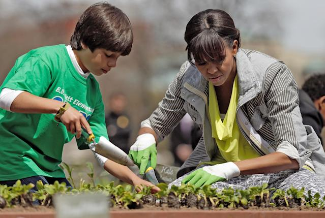 "WASHINGTON, DC - APRIL 04: U.S. first lady Michelle Obama plants the White House Kitchen Garden with fifth grader Emilo Vega of Florida on the South Lawn of the White House April 4, 2013 in Washington, DC. For the fifth time, the first lady invited students from ""schools that have made exceptional improvements to school lunches from Florida, Massachusetts, Tennessee and Vermont to help her plant the garden. (Photo by Win McNamee/Getty Images)"