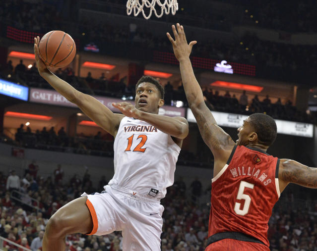 Virginia guard De'Andre Hunter (12) attempts a shot over the reach of Louisville center Malik Williams (5) during the first half of an NCAA college basketball game in Louisville, Ky., Saturday, Feb. 23, 2019. (AP Photo/Timothy D. Easley)