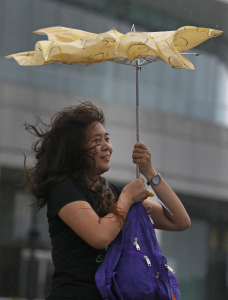 A tourist from mainland China braves strong wind near the waterfront in Hong Kong Sunday, Sept. 22, 2013. The year's most powerful typhoon had Hong Kong in its crosshairs on Sunday after sweeping past the Philippines and Taiwan and pummeling island communities with heavy rains and fierce winds. Typhoon Usagi was grinding westward and expected to make landfall close to Hong Kong late Sunday or early Monday. (AP Photo/Vincent Yu)