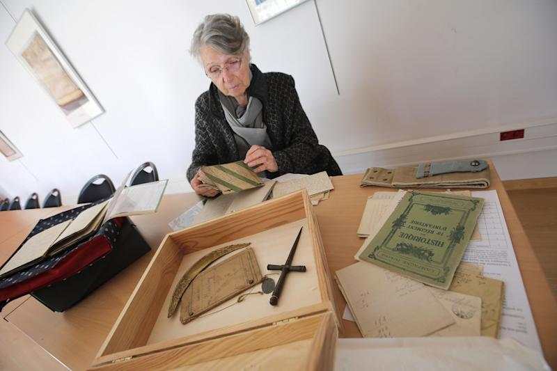 "In this photo taken Wednesday Nov. 13, 2013, Josette Faraut prepares some family pictures, documents and items dating from World War I, in Nice, southern France. Paris' National Library is one of dozens of collection points across France that opened their doors from November 9 to 16 for the ""Grande Collecte."" Donors were invited to tell the stories behind their mementos, which the library's experts used to annotate the entries in the archive. Contributors watched as the library's technical staff digitized their items before returning them to the donor. (AP Photo/Lionel Cironneau)"