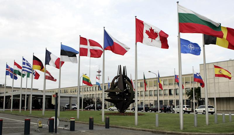 File - In this Thursday, June 14, 2007 file photo, NATO member country flags are seen outside NATO headquarters in Brussels. A spokeswoman on Sunday, June 24, 2012 said NATO's governing body will meet Tuesday, June 26, 2012 to discuss the Syrian downing of a Turkish plane. Turkish officials say a jet was on a training flight Friday when it strayed into Syrian airspace, but was in international airspace when it was shot down. (AP Photo/Virginia Mayo File)