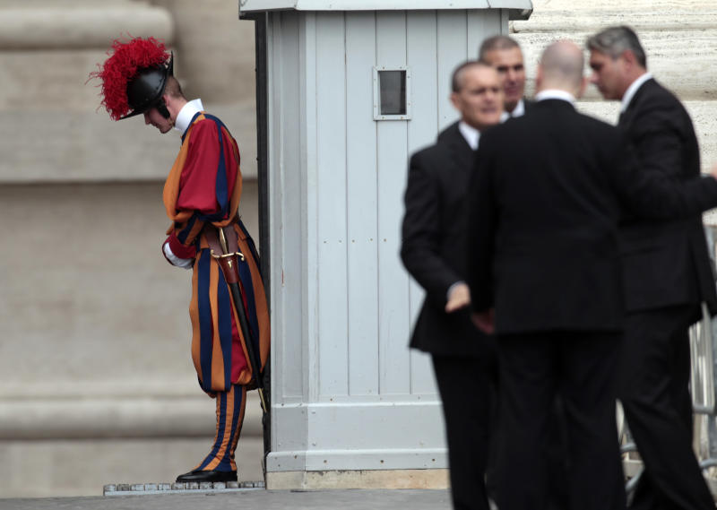 A Vatican Swiss guard and Vatican security staff wait for the arrival of Pope Benedict XVI at the weekly general audience in St. Peter's square at the Vatican, Wednesday, Sept. 26, 2012. Pope Benedict XVI's ex-butler and another Vatican lay employee are scheduled to go on trial Saturday in the embarrassing theft of papal documents that exposed alleged corruption at the Holy See's highest levels. (AP Photo/Gregorio Borgia)