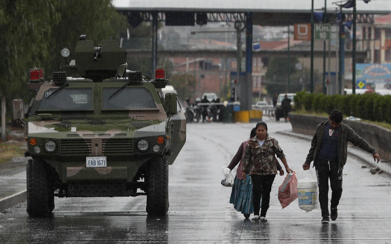 People walk past a military armored vehicle patrolling in Sacaba, Bolivia, Thursday, Nov. 14, 2019. Bolivia's former President Evo Morales resigned and flew to Mexico under military pressure following massive nationwide protests over alleged fraud in an election last month in which he claimed to have won a fourth term in office. (AP Photo/Juan Karita)