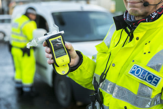 A PSNI Road Policing officer holds an operational breathalyser during a random drink driving checkpoint in Belfast.