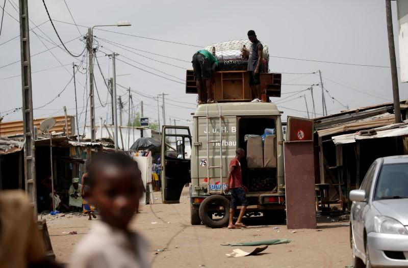 People gather their belongings as they prepare to leave their houses at Adjoufou in the area around Felix Houphouet Boigny airport in Abidjan