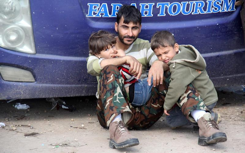 A Syrian man and his children who arrived a day earlier from government-held villages of Fuaa and Kafraya wait in rebel-held Rashidin, west of Aleppo city, following delays in evacuating them as the hard-won evacuation deal ran into trouble on April 15, 2017.  - Credit: AFP