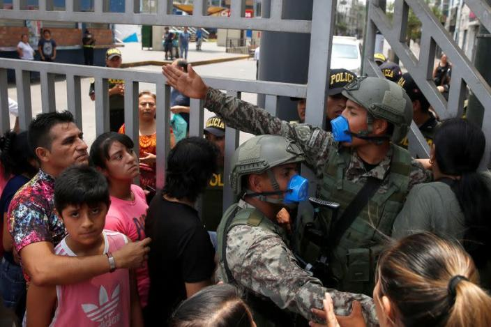 Soldiers control the access to the Gamarra textile market after Peru's government deployed military personnel to block major roads, as the country rolled out a 15-day state of emergency to slow the spread of coronavirus disease (COVID-19), in Lima