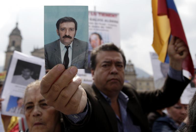A man shows a photo of a missing person during a protest organized by activists and relatives of people allegedly disappeared by rebels, in Bogota, Colombia, Sunday, Oct. 14, 2012. Demonstrators demanded participation in the peace talks between Colombia's government and Colombia's main leftist rebel movement, FARC, that will start on Monday in Norway. (AP Photo/Fernando Vergara)