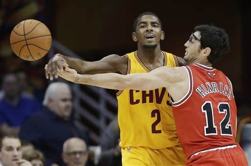 Cleveland Cavaliers' Kyrie Irving (2) passes around Chicago Bulls' Kirk Hinrich during the first quarter of an NBA basketball game Friday, Nov. 2, 2012, in Cleveland. (AP Photo/Mark Duncan)