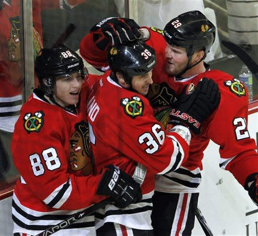 Chicago Blackhawks' Dave Bollard (36) gets congratulations from teammates Patrick Kane, left, and Bryan Bickell after Bollard scored against the St. Louis Blues in the third period of an NHL game Sunday, Feb. 19, 2012, in Chicago. Chicago won 3-1. (AP Photo/John Smierciak)