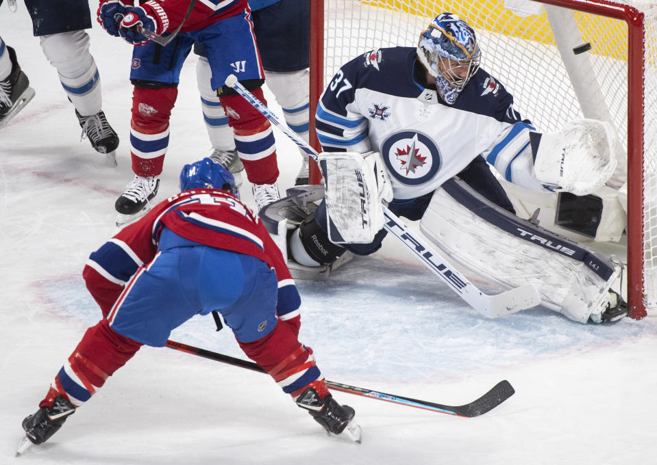 Montreal Canadiens' Brendan Gallagher (11) scores against Winnipeg Jets goaltender Connor Hellebuyck during the second period of an NHL hockey game Saturday, March 6, 2021, in Montreal. (Graham Hughes/The Canadian Press vIa AP)