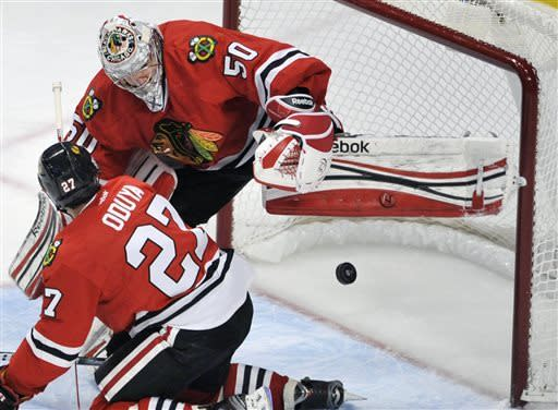 Chicago Blackhawks goalie Corey Crawford makes a save against the St. Louis Blues while teammate Johnny Oduya looks on during the first period of an NHL hockey game in Chicago, Thursday, April 4, 2013. (AP Photo/Paul Beaty)