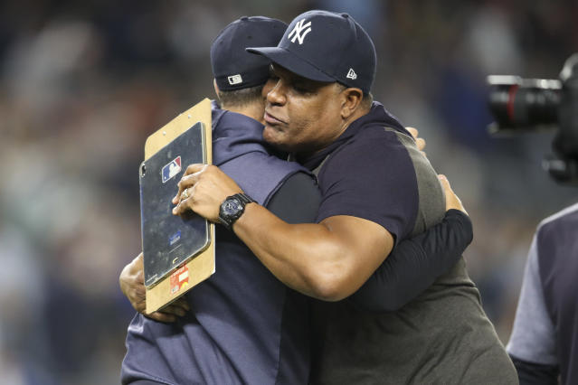 CORRECTS TO BULLPEN COACH MIKE HARKEY, INSTEAD OF PITCHER CC SABATHIA - New York Yankees bullpen coach Mike Harkey, right, embraces manager Aaron Boone after the Yankees defeated the Los Angeles Angels 9-1 in a baseball game and clinched the AL East title Thursday, Sept. 19, 2019, in New York. (AP Photo/Mary Altaffer)