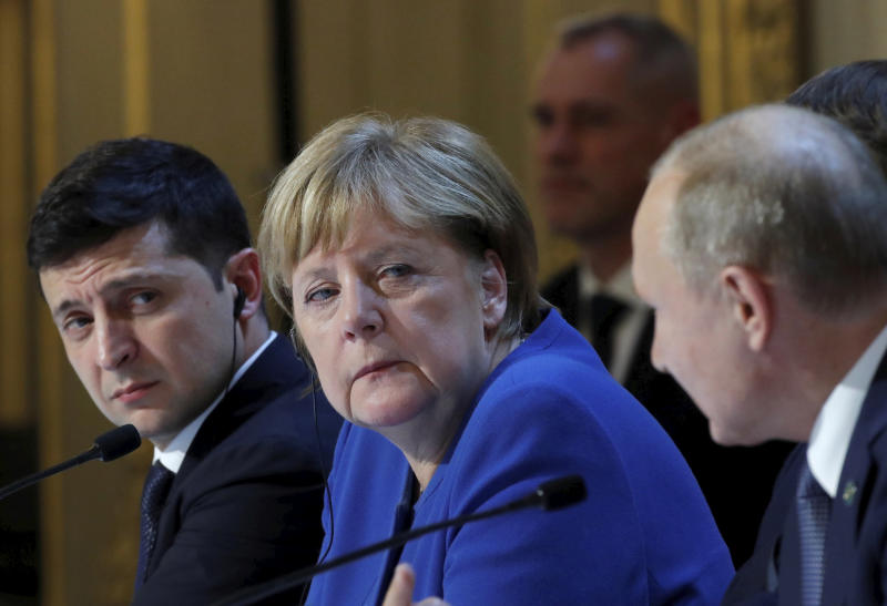Ukraine's President Volodymyr Zelenskiy, left, German Chancellor Angela Merkel and Russian President Vladimir Putin, right, attend a joint news conference with French President Emmanuel Macron at the Elysee Palace in Paris, Monday Dec. 9, 2019. Russian President Vladimir Putin and Ukrainian President Volodymyr Zelenskiy met for the first time Monday at a summit in Paris to try to end five years of war between Ukrainian troops and Russian-backed separatists. (Charles Platiau/Pool via AP)
